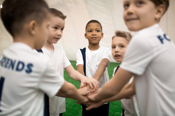 Little soccer players in uniform making pile of hands to express teambuilding