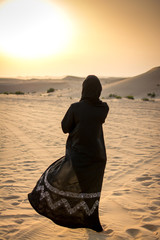 Woman in a burka Burqa walking over a middle eastern desert during sunset.