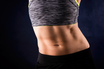 Woman`s flat stomach with press. ABS. Sport style. Isolated on dark blue background. Workout and healthy concept