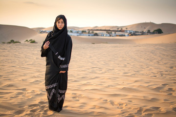 Full length portrait of Arabic woman in traditional black clothes standing in the desert in front of Bedouin village.