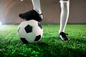 Young soccer player in boots and socks keeping one foot on ball while standing on green lawn