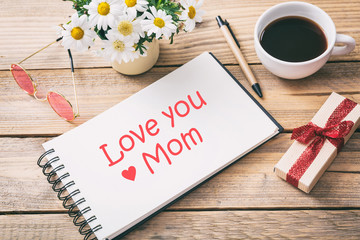 Gift box and love you mom written on the notebook, office desk background