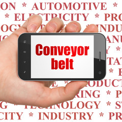 Manufacuring concept: Hand Holding Smartphone with  red text Conveyor Belt on display,  Tag Cloud background, 3D rendering