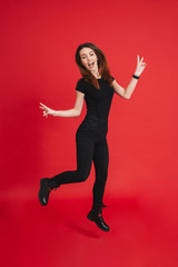 Full-length photo of splendid woman 20s in black clothing having fun and gesturing peace sign with both hands, isolated over red background