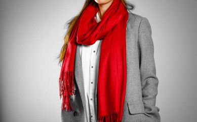 Girl in grey coat and red scarf. Isolated on grey background