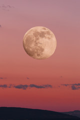 red sky during sunset with a big moon in the full moon phase and the silhouette of a small plane. image of nature without people. image of the moon with tinting in red.