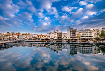 Agios Nikolaos Crete -Amazing view with reflections at Voulismeni lake. Dramatic sky with colorful buildings of one of the most popular touristic destination of Crete.