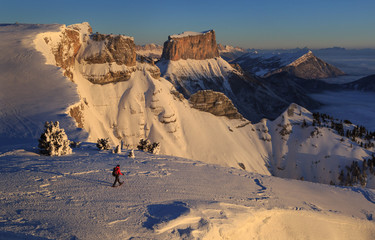 Fotomurales - Hiker on snowshoes walking in  the snowcovered Vercors during a winter sunrise.