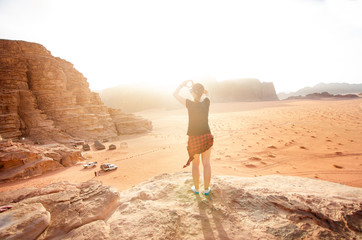 Person on a top of mountains in a desert. Sunset view. Nature. Tourist people enjoy a moment in a nature. Wadi rum national park - Jordan