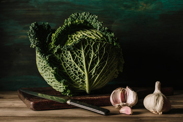 Delicious fresh and big cabbage with garlics in a wooden table.
