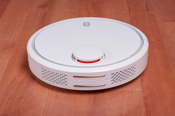 White robot vacuum cleaner on laminate floor cleaning dust in living room. Modern smart electronic housekeeping technology