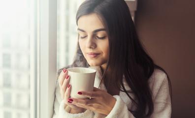 Beautiful girl wears white bathrobe smells cup of coffee sitting on the windowsill near window