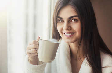 Beautiful girl wears white bathrobe holding cup of coffee near window