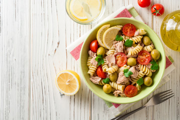 Fusilli pasta salad with tuna, tomatoes, olives and parsley on white wooden background.
