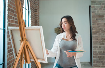 Beautiful young woman painting on a canvas in art studio