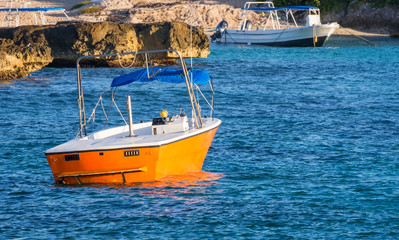 Small bright orange fishing boat, tourist boat at a tropical island