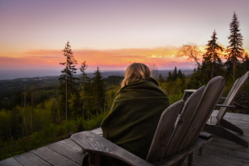 Woman in blanket on wooden chair watches sun rise over forest