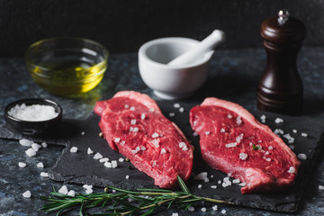 Two raw picanha steaks on a cutting board with spices on a dark background