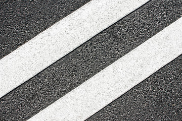 Road white double paint lines on gray asphalt. Transportation background.