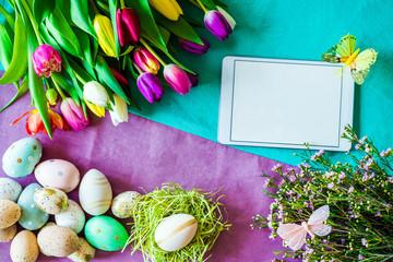 Freifläche auf Tablet mit buntem Hintergrund und Tulpen im Frühling, Ostereier von oben zu Ostern