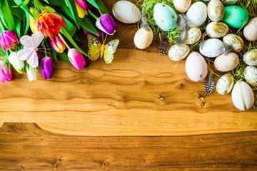 Freifläche auf Holztisch im Hintergrund und Osterdekoration wie bunte verzierte Ostereier, Federn, Schmetterlinge und Tulpen von oben zu Ostern