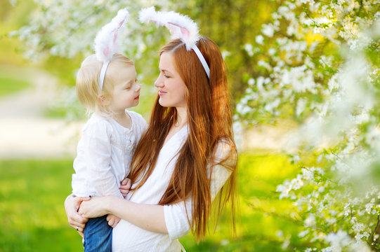 Young mother and her daughter wearing bunny ears in a spring garden on Easter day
