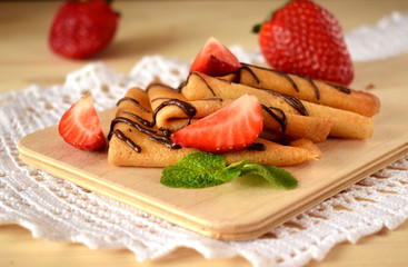 Golden crepes with fresh strawberries and mint on a wooden board