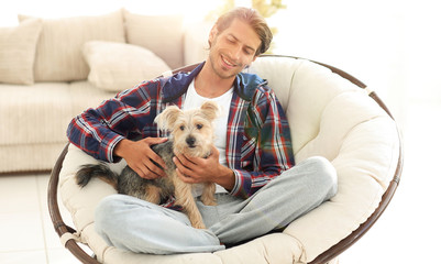 handsome guy with a dog sitting in a large armchair.