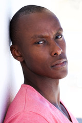 Close up handsome african man leaning against white wall