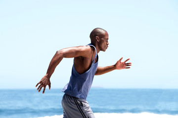 african american male runner outside by sea