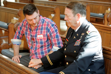Colonel Allen Queen holds hands with his son Travis Queen as they pray in the Chatlos Memorial Chapel, where a memorial for evangelist Billy Graham took place on the grounds of the Billy Graham Training Center in Asheville