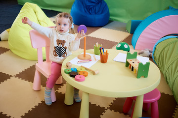 Little girl drawing with color pencils - sitting at the table with her toy bear