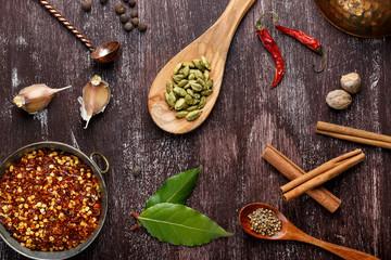 Various spices on dark brown background.