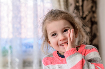 a little girl with shiny brown eyes, long eyelashes and puffy cheeks in a striped pink-white-gray sweater smiles and bites her thumb