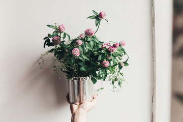 hand holding clover bouquet with pink flowers in metallic cane. wildflowers in rustic rural home. country slow living