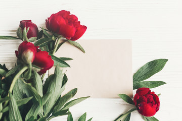 floral greeting card concept, hello spring stylish image flat lay. beautiful red peonies  bouquet on white wooden rustic background, top view. space for text. happy womens mothers day