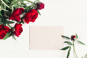 beautiful red peonies bouquet and craft paper card on white wooden rustic background, flat lay. modern greeting card with space for text. top view. happy womens day or mothers