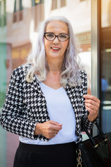 Stylish woman in a trendy black and white outfit carrying a handbag standing in town in front of a large glass window smiling at the camera