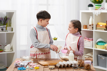 Girl and boy cooking in home kitchen, make the dough for baking, healthy food concept