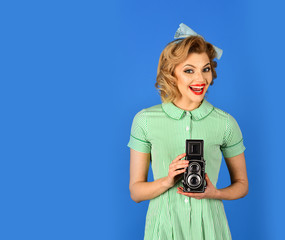 Photo of beautiful pin-up girl with old camera