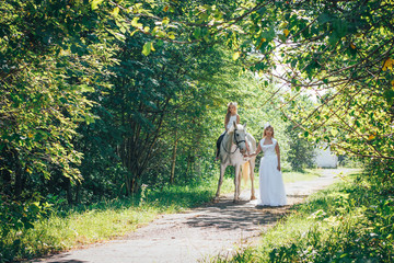 Bride, small girl and white horse in the park