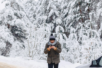 a guy walking along a snow-covered road near a pine forest with phone