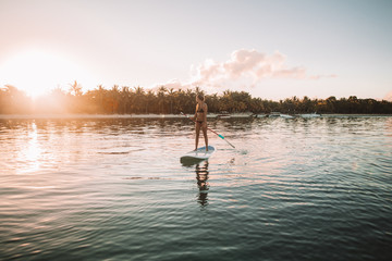 Woman paddleboarding in sea against sky during sunset