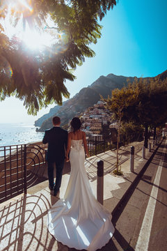 Tender romantic young couple in honeymoon after wedding in Positano, Amalfi coast, Italy