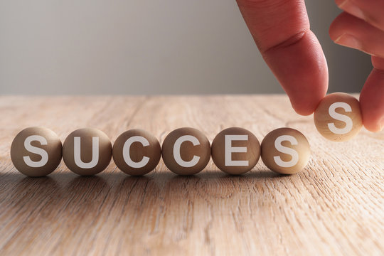 Hand putting on success word written in wooden cube