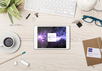 Tablet and Business Card at Wooden Desk with Accessories Mockup 1
