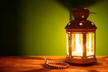 Holy month of Ramadan Karim background. Bright lantern and beads on the table with a copy space