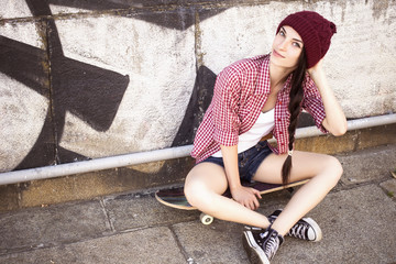Brunette teenage girl in hipster outfit (jeans shorts, keds, plaid shirt, hat) with a skateboard at the park outdoors