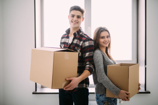 Couple with boxes moving into new home smiling. young couple on moving day.