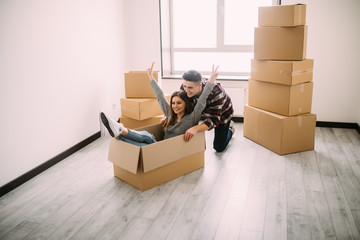 The young woman sitting in a cardboard box. Moving, purchase of new habitation.